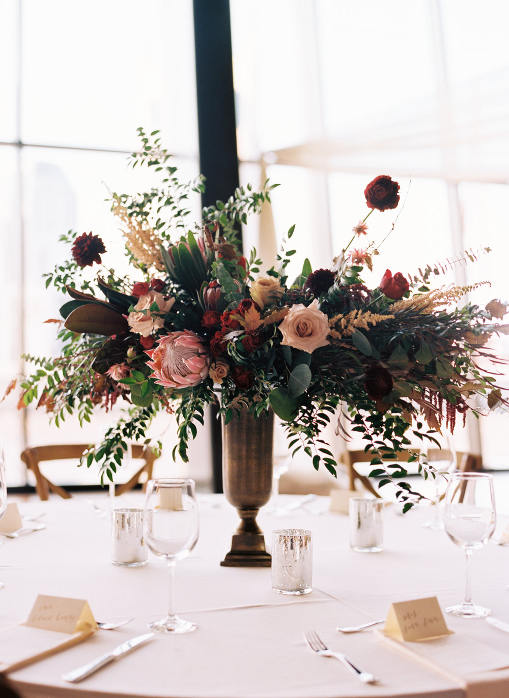 Centerpieces with marsala dahlias, burgundy ranunculus, peach astilbe, protea, and natural greenery // Nashville Wedding Florist // Country Music Hall of Fame