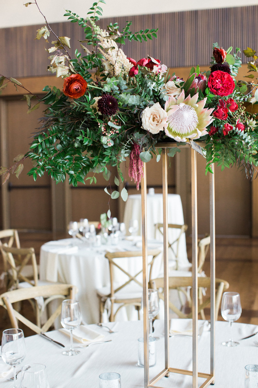 Lush, untamed elevated centerpiece with king protea, marsala dahlias, soft peach astilbe, and natural greenery // Nashville Wedding Floral Design