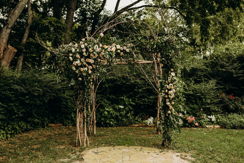 Branchy arbor with lush, untamed greenery and blush flowers // Nashville Wedding Florist