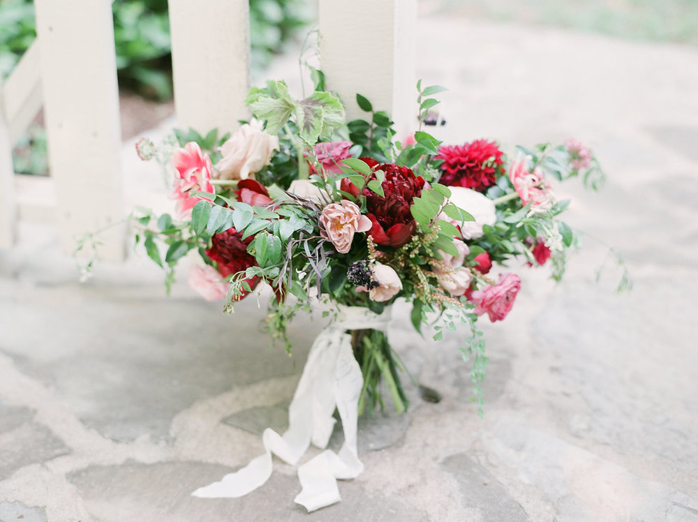 Bridal bouquet with marsala peonies, dahlias, tulips, and natural greenery