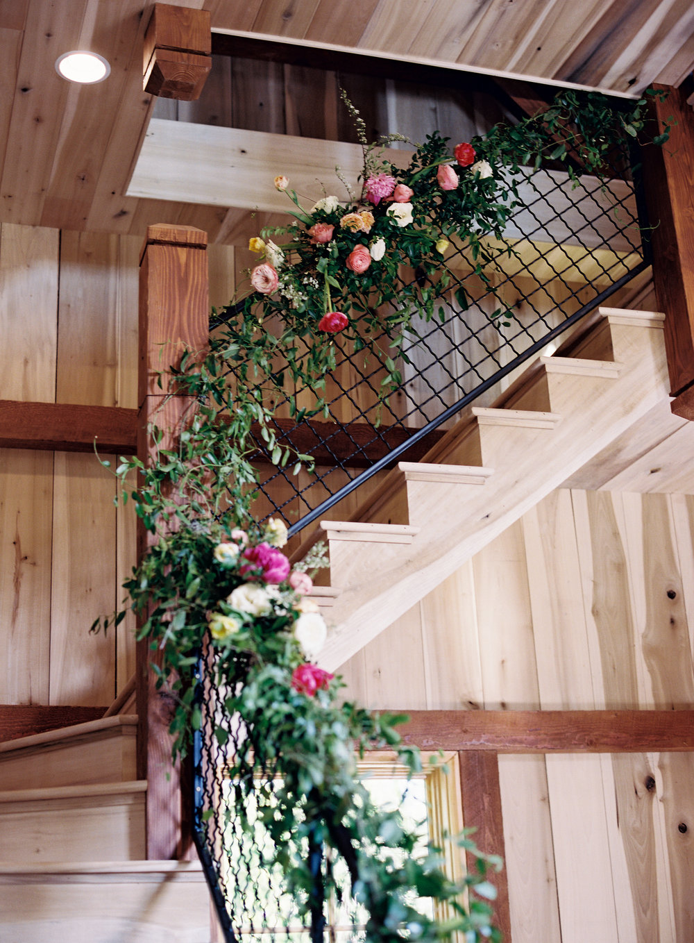 Stairwell garland with bright floral accents // Nashville Barn Wedding Florist