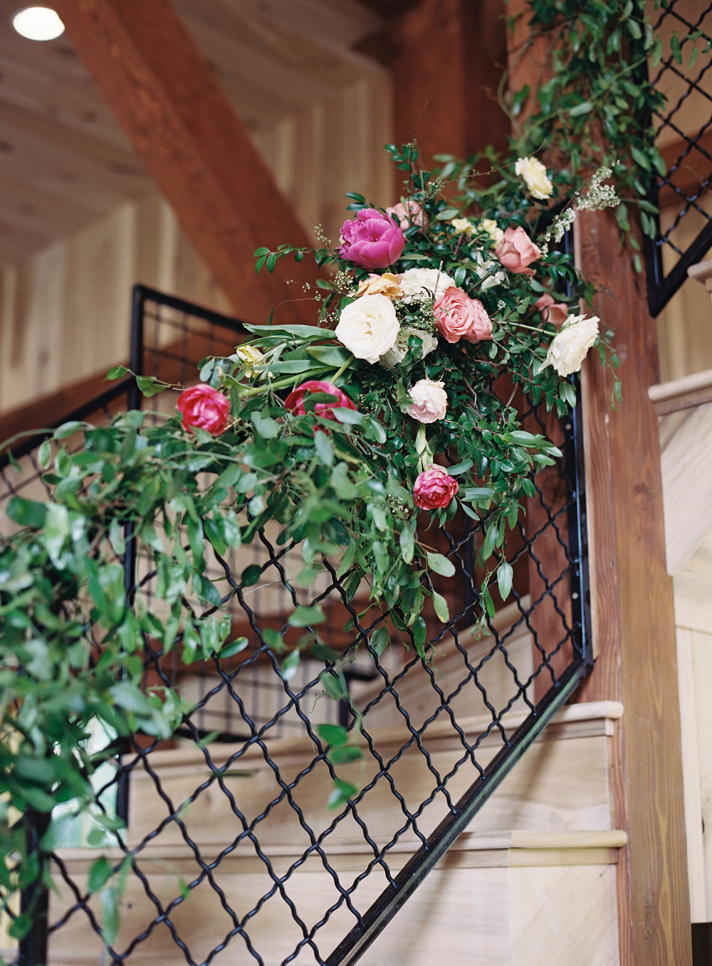 Lush vines trailing down the stairwell with pink and peach floral pops // Nashville Wedding Floral Design