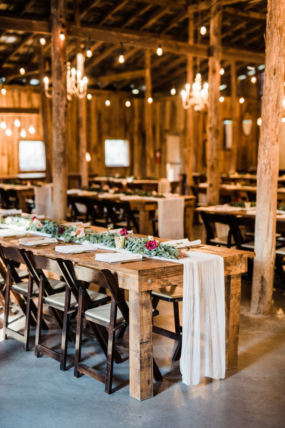 Barn reception with lush greenery table runners // Nashville Wedding Florist