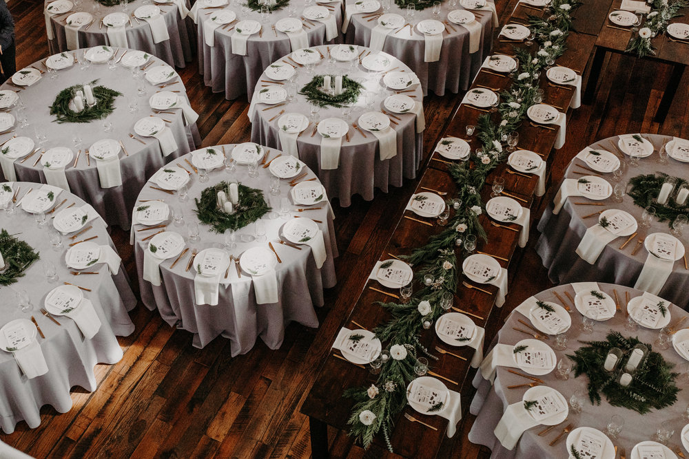 Loose greenery and white pillar candles centerpieces // Nashville Wedding Floral Design