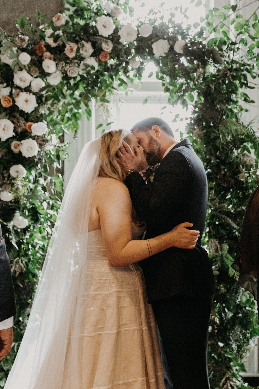 First kiss under a profusion of flowers  // Nashville Wedding Florist