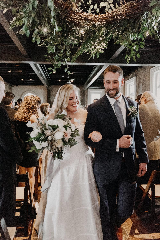 Recessional under a lush wreath of greenery  // Nashville Wedding Floral Design