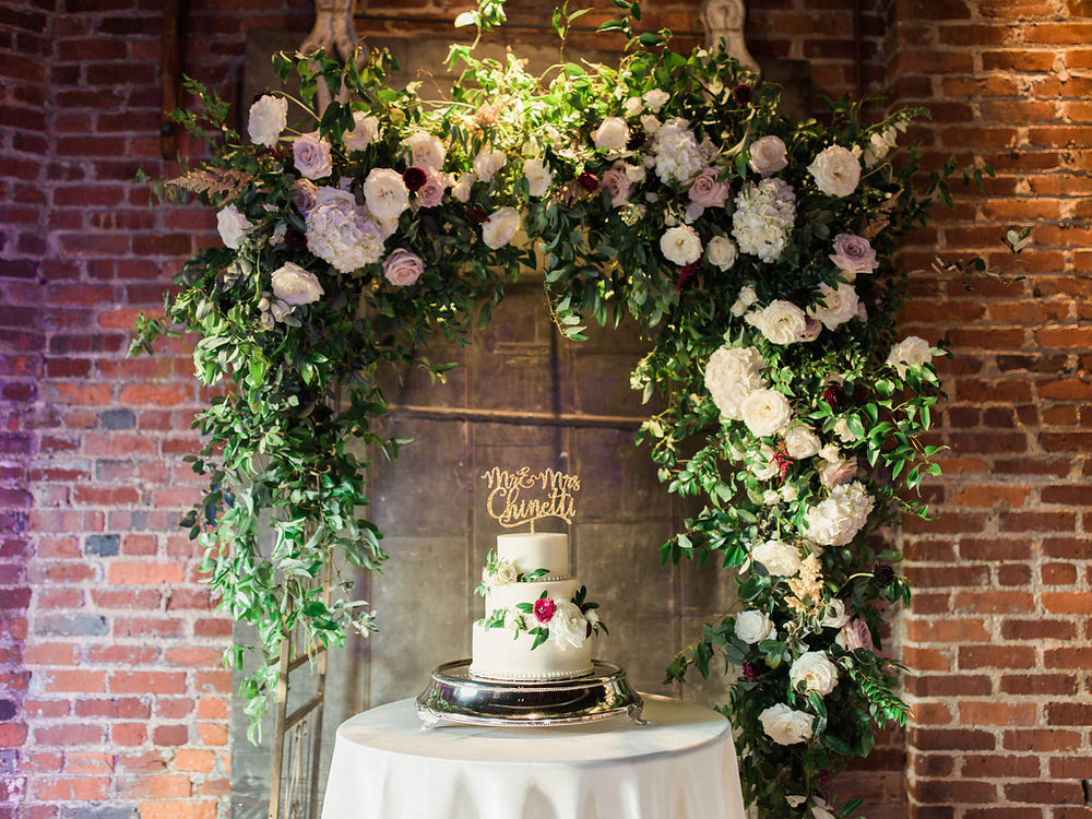 Lush garden arch with natural greenery behind the cake // Nashville Wedding Floral Design