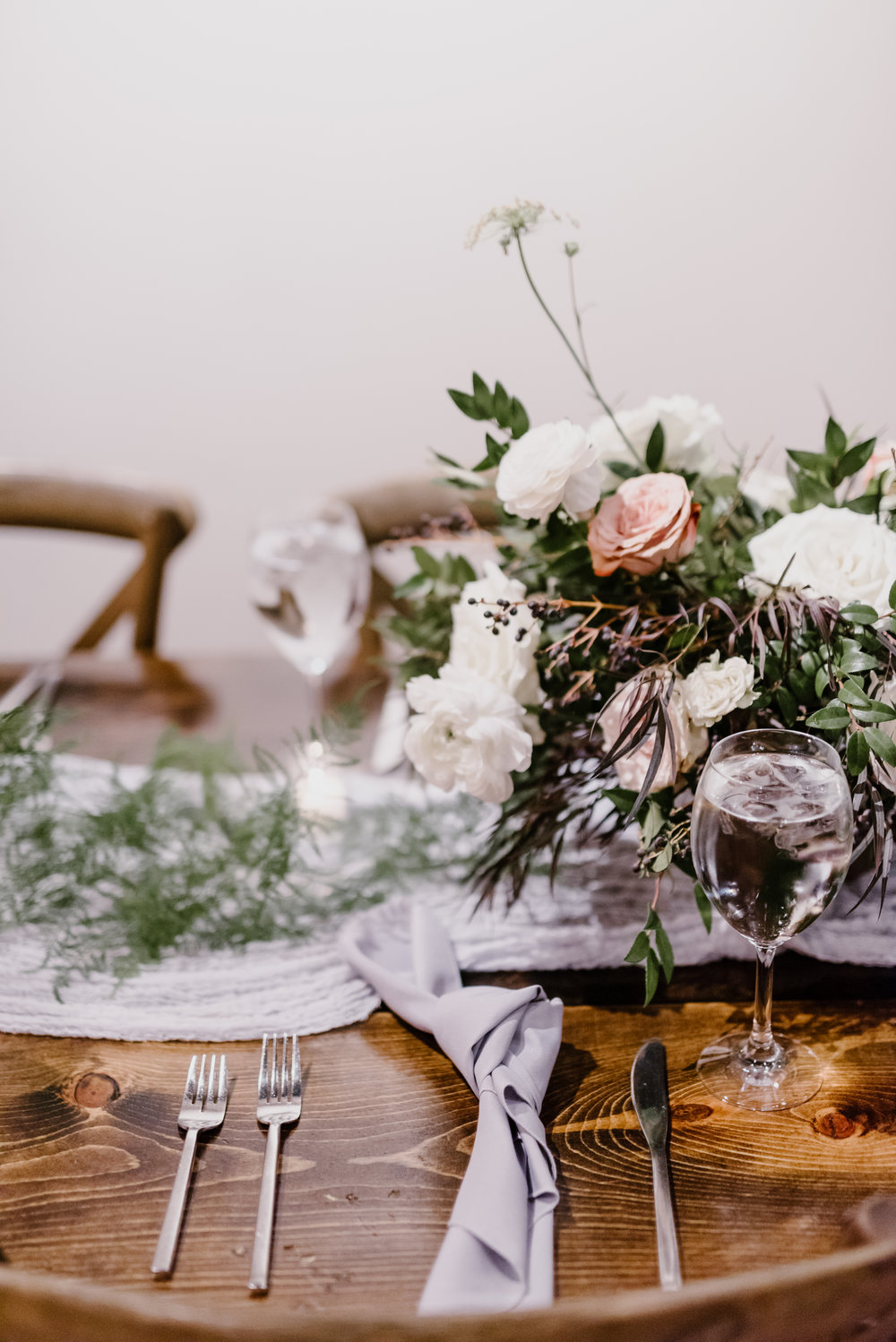 Low, organic centerpiece with garden roses, ranunculus, and trailing greenery // Southeastern Wedding Floral Design