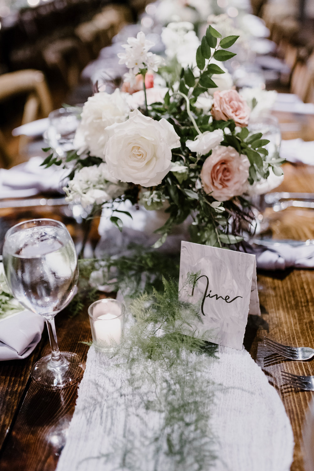 Low, overflowing centerpiece with soft grey runners and light, airy greenery // Cordelle Wedding Flowers