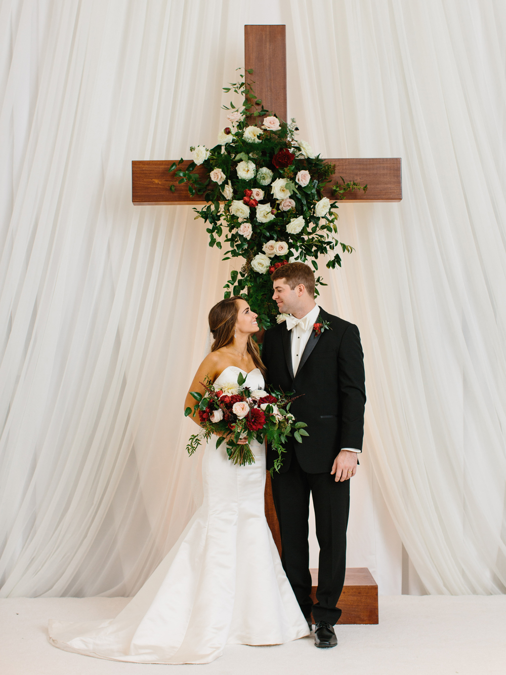 Large wooden cross for the ceremony backdrop with a lush floral spray of garden roses, dahlias, and greenery // Nashville Wedding Floral Design