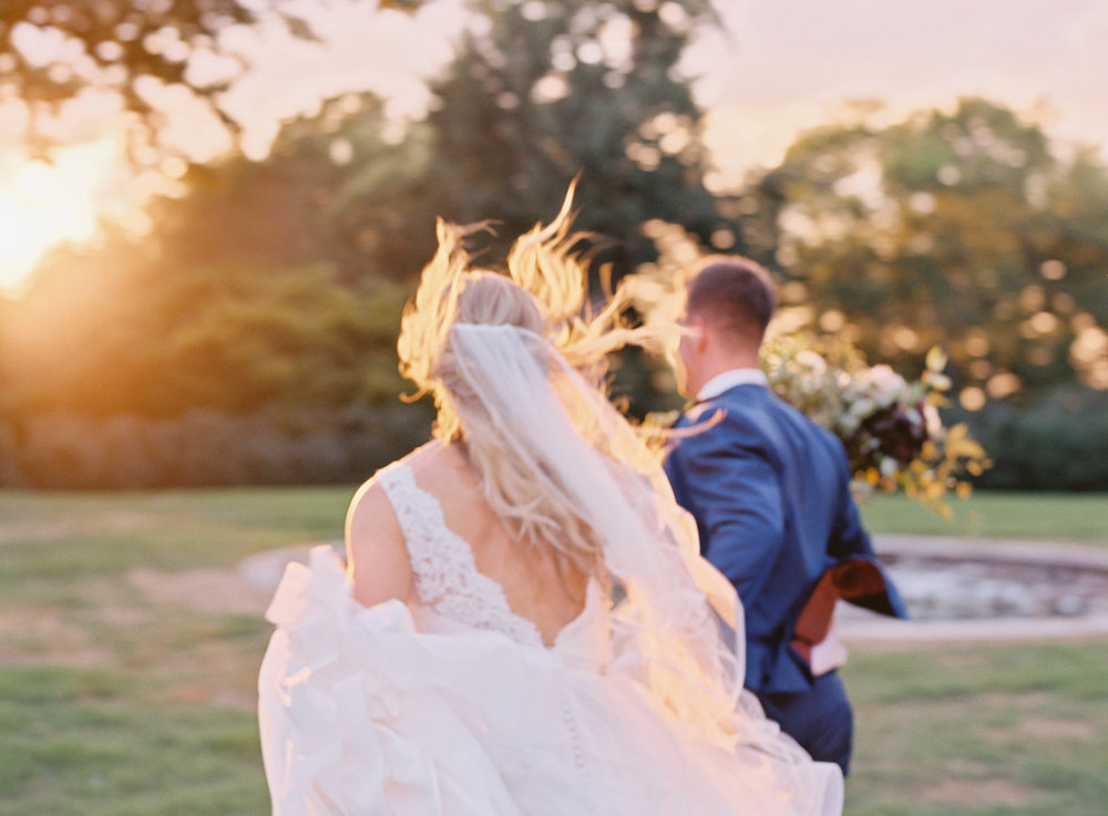 Bride and groom running towards the sunset // Nashville Wedding Florist