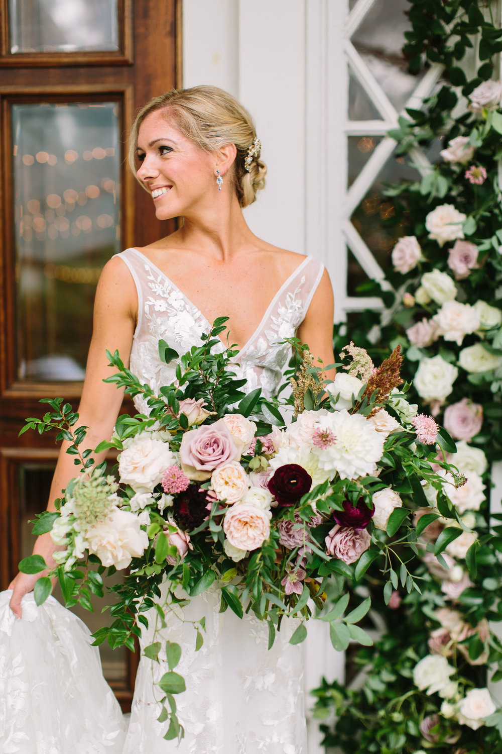 Natural, asymmetrical bridal bouquet with soft mauve garden roses, eggplant ranunculus, and trailing greenery // Nashville Wedding Floral Design