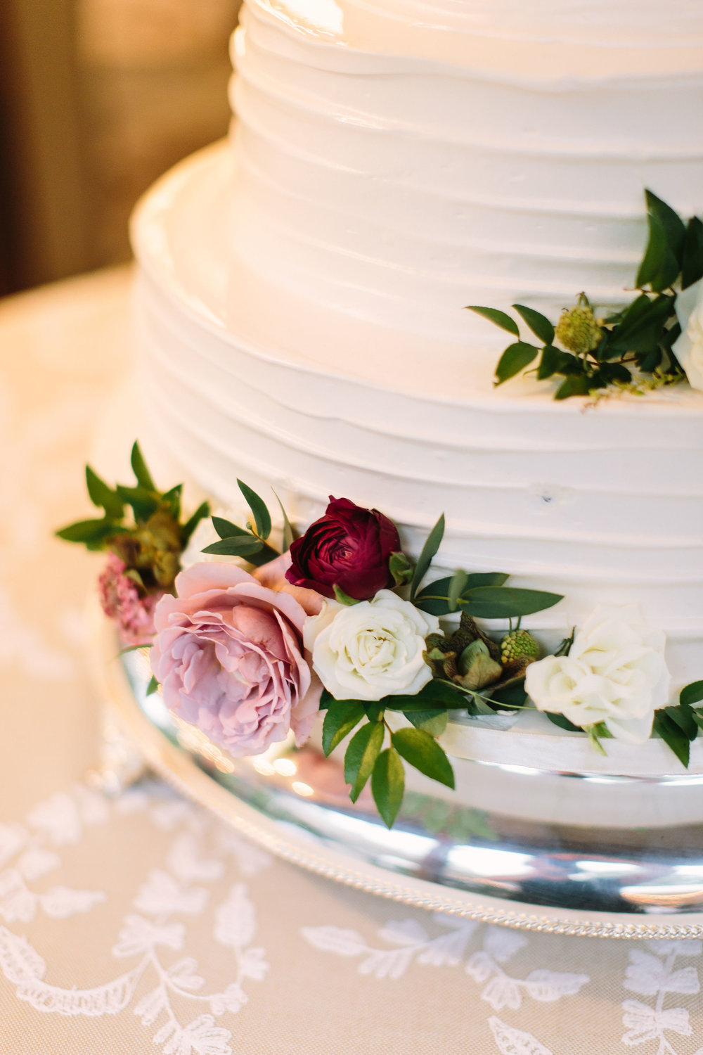 White, 4-tired wedding cake with clustered floral accents using garden roses, ranunculus, hellebores, and greenery // Nashville Wedding Floral Design