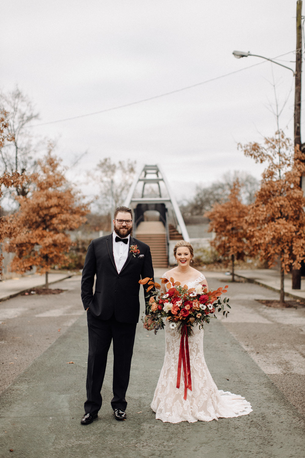 Asymmetrical, airy bridal bouquet with burgundy, burnt orange, and gold hues, using anemones, dahlias, and garden roses. Nashville, TN wedding florist.