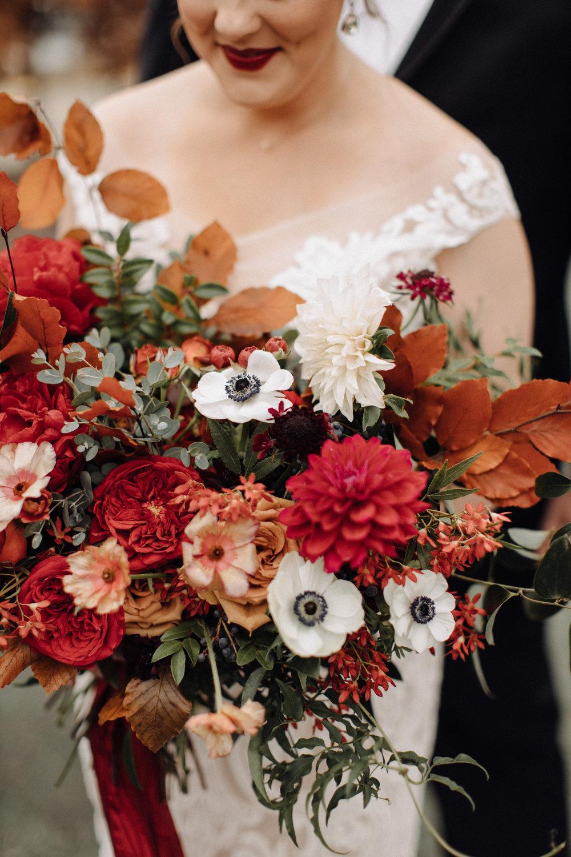 Lush bridal bouquet with autumn foliage, anemones, dahlias, and garden roses. Nashville Wedding Floral Design.