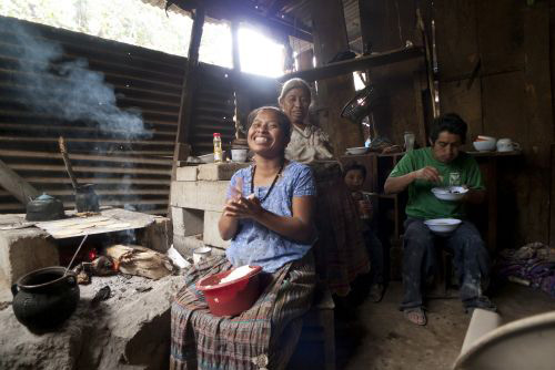 A Guatemalan family sharing the cooking and eating of a meal in a typical Guatemalan house.