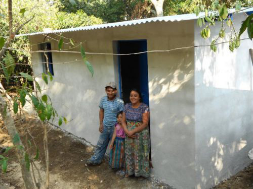 The family stands in the doorway of their newly built house.