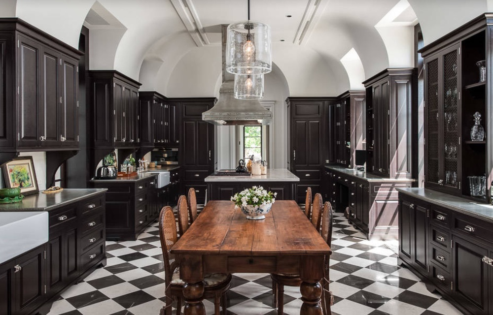 Black cabinetry with checkerboard floor and antique farmhouse table - Design by Alonso and Associates