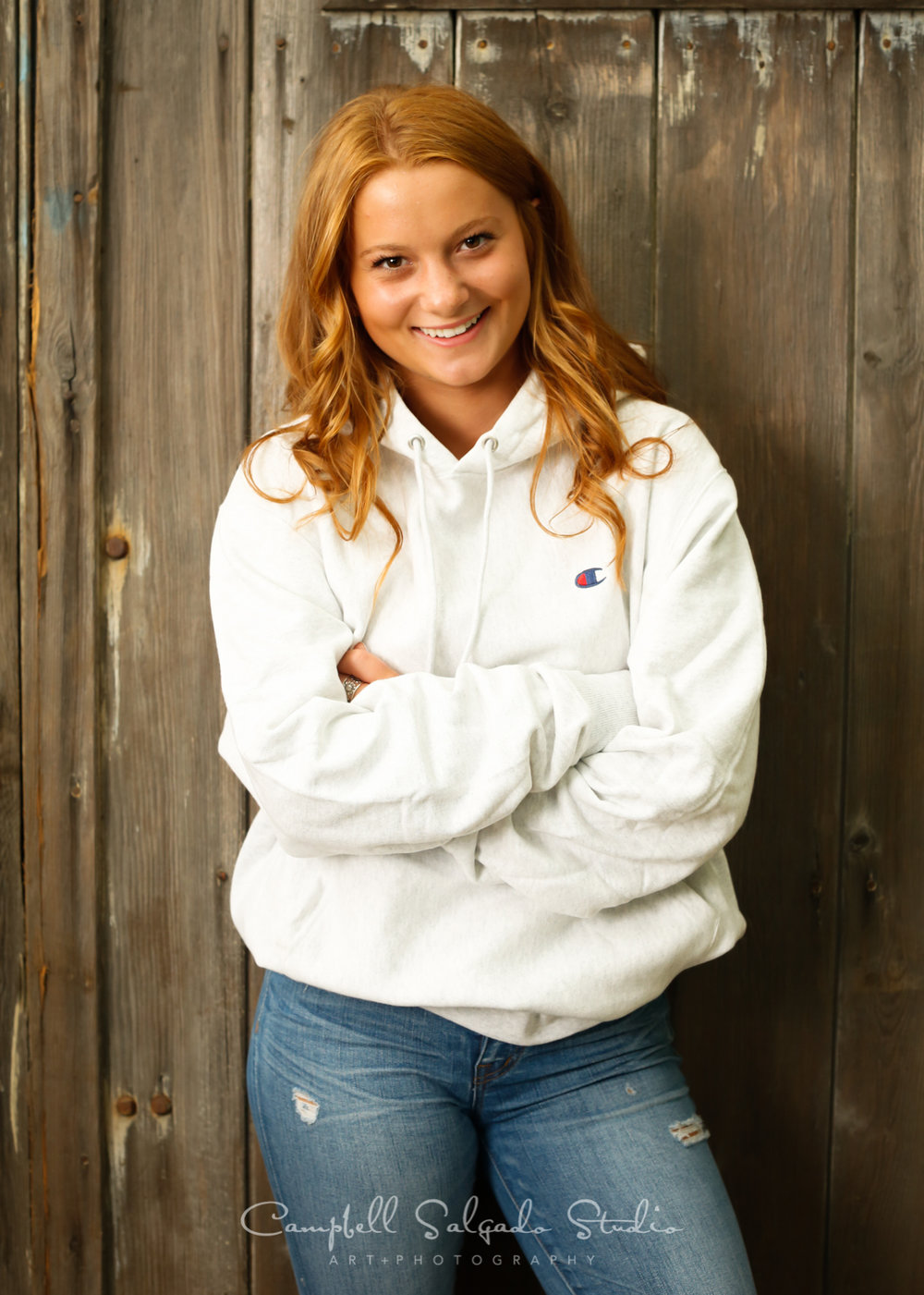 Portrait of high school senior on barn doors background by teen photographers at Campbell Salgado Studio in Portland, Oregon.