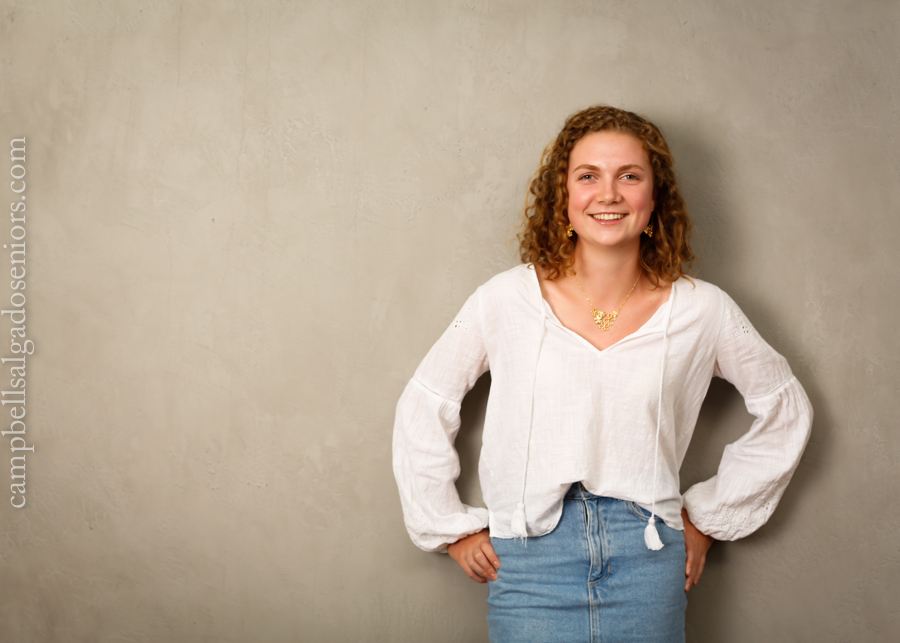 Portrait of high school senior on modern grey background by teen photographers at Campbell Salgado Studio in Portland, Oregon.