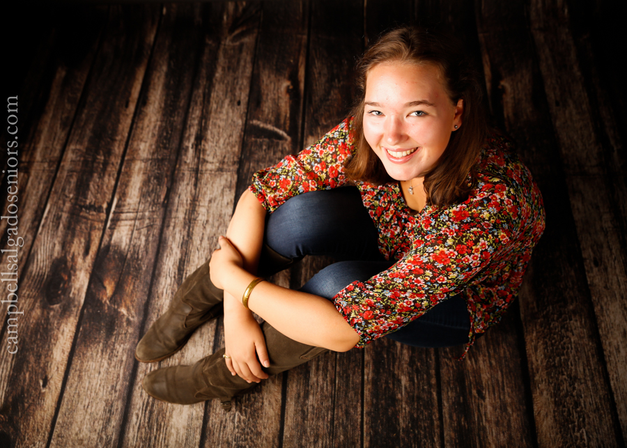 Portrait of high school senior on wooden floor background by teen photographers at Campbell Salgado Studio in Portland, Oregon.