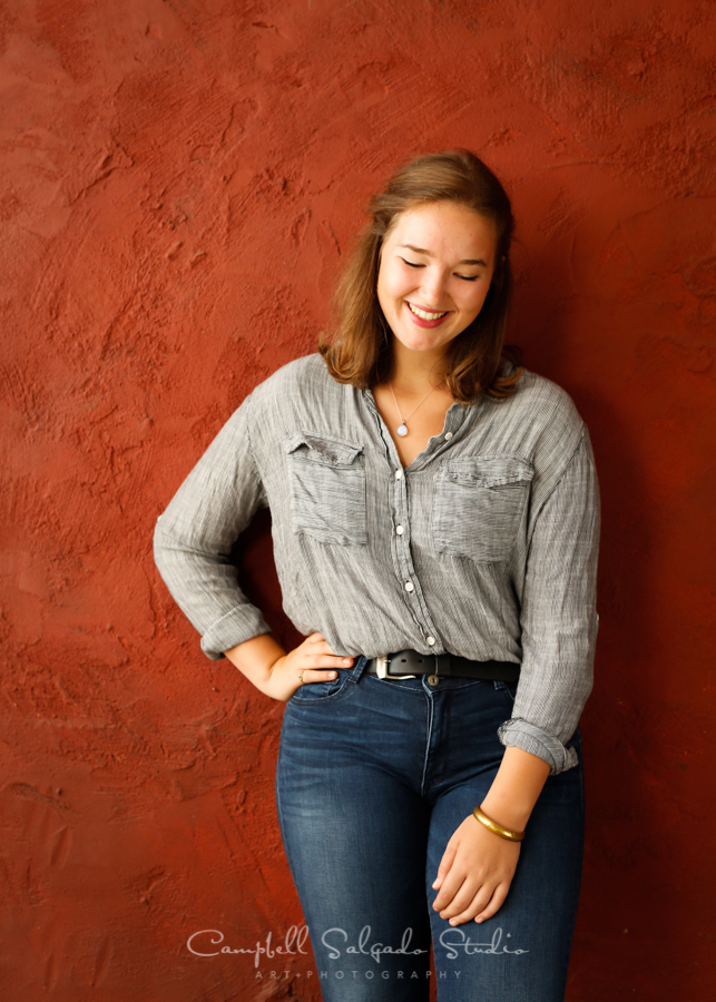 Portrait of high school senior on red stucco background by teen photographers at Campbell Salgado Studio in Portland, Oregon.