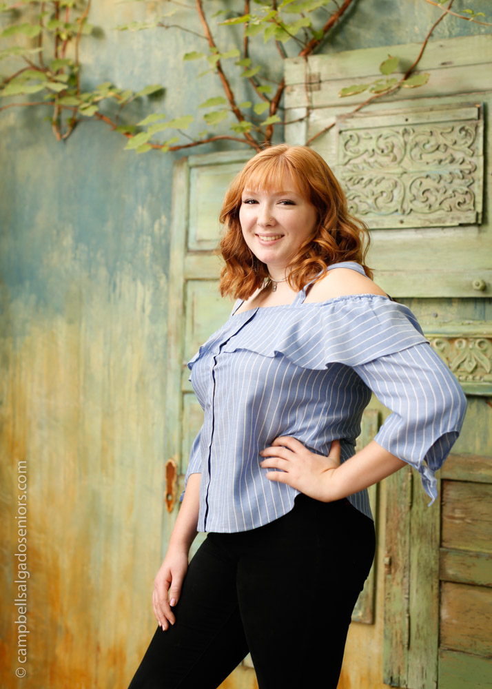 Portrait of high school senior on vintage green doors background by teen photographers at Campbell Salgado Studio in Portland, Oregon.