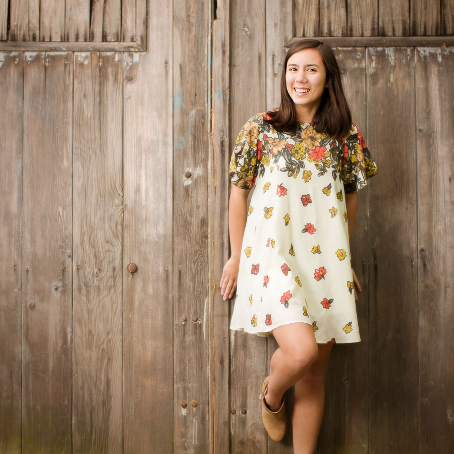 Young woman in front of barn doors in a outdoor Campbell Salgado Studio for her high school senior pictures session. Wearing gray and purple against green foliage.
