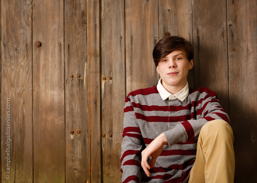enior portraits, Portland Oregon of young man in front of a barn door background by high school senior photographer at Campbell Salgado Studio.