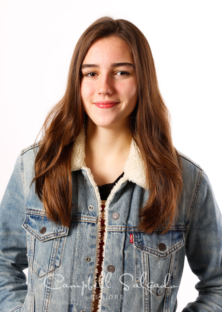 High school senior pictures of a young woman standing in front of white background by senior photographers at Campbell Salgado Studio in Portland, Oregon.