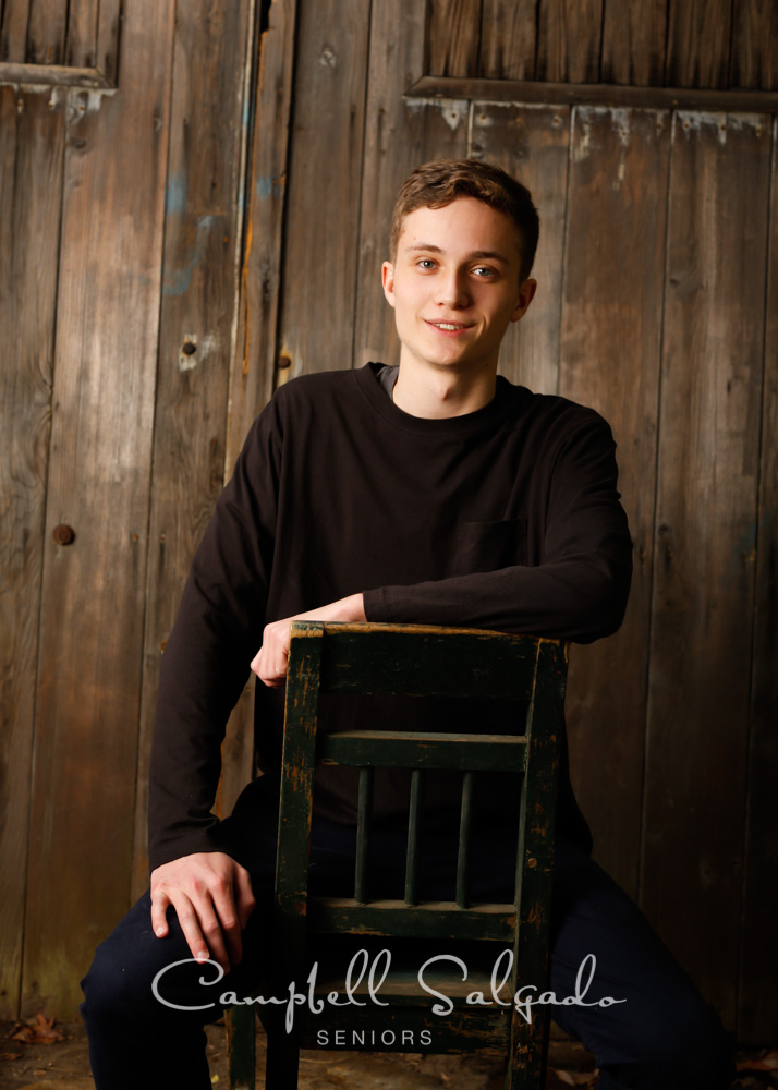 Senior picture of a young man in barn doors background by high school senior photographers at Campbell Salgado Studio in Portland, Oregon.