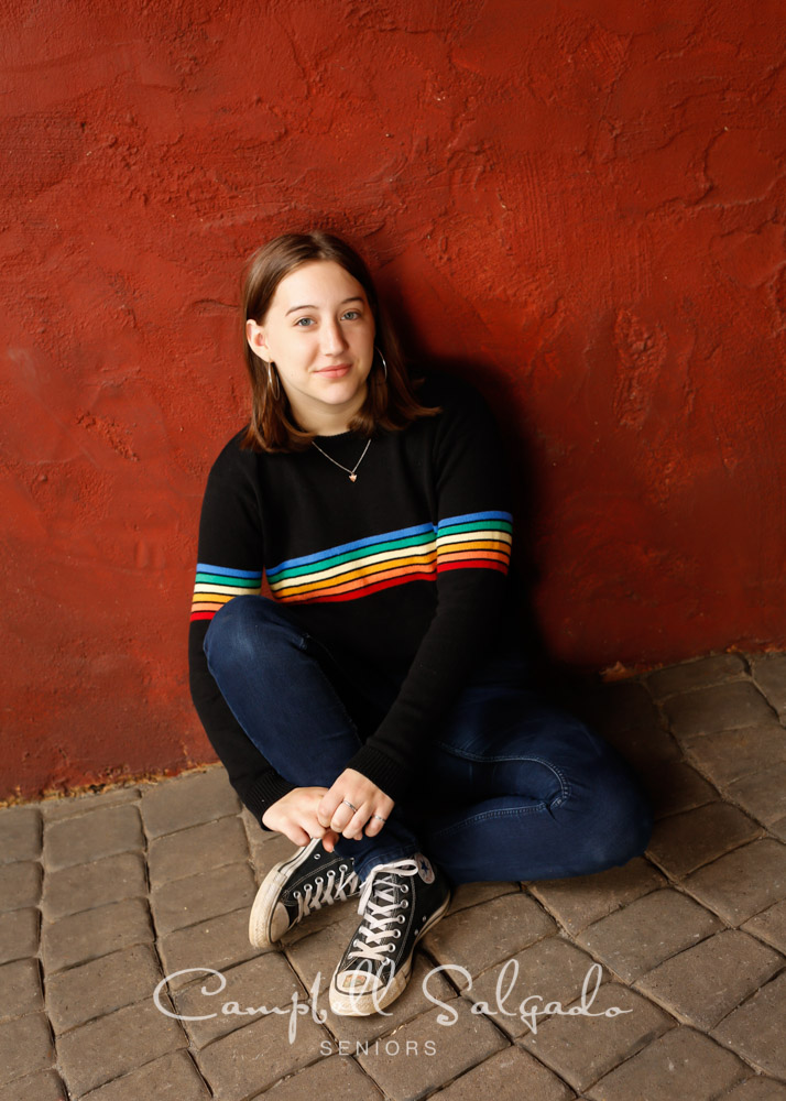 Senior portraits outside of a young woman in front of a red stucco background by high school senior picture photographers photographers at Campbell Salgado Studio in Portland, Oregon.