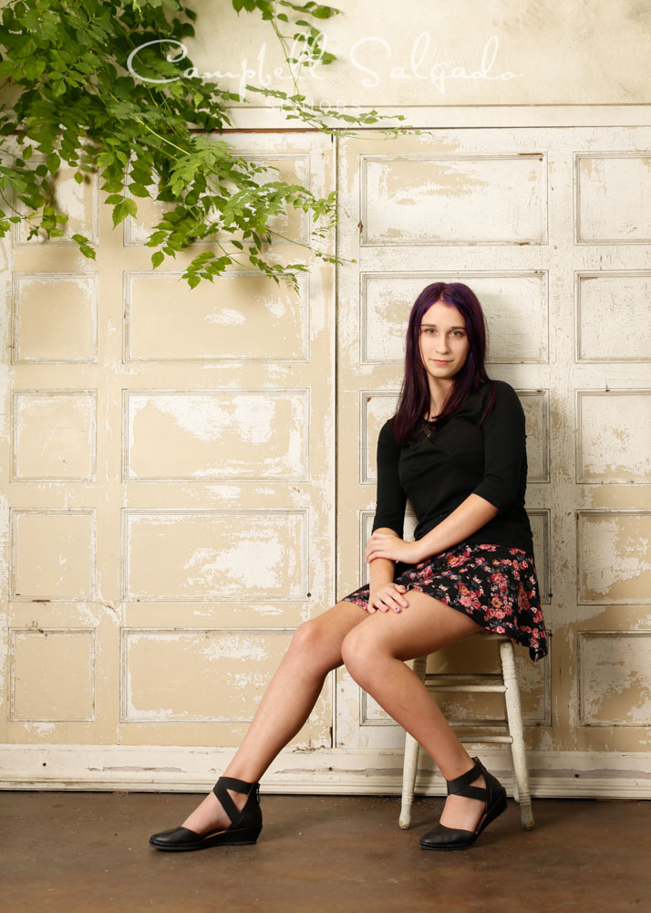 Portrait of young woman against a antique ivory door background by Portland photographers - senior pictures at Campbell Salgado Studio in Portland, Oregon.