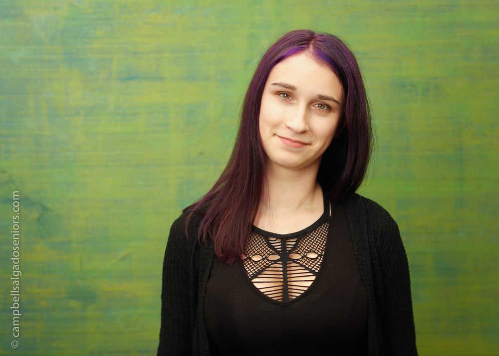 Senior portraits, Portland Oregon of young woman in front of a blue-green weave background by photographers at Campbell Salgado Studio.