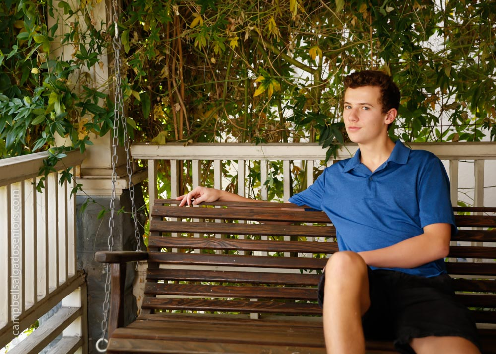 High school senior portrait photography of teen on porch swing background by senior picture photographers at Campbell Salgado Studio in Portland, Oregon.