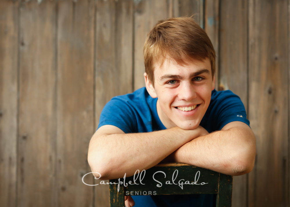 Senior portraits outside of a young man in front of a barn doors background by high school senior picture photographers photographers at Campbell Salgado Studio in Portland, Oregon.