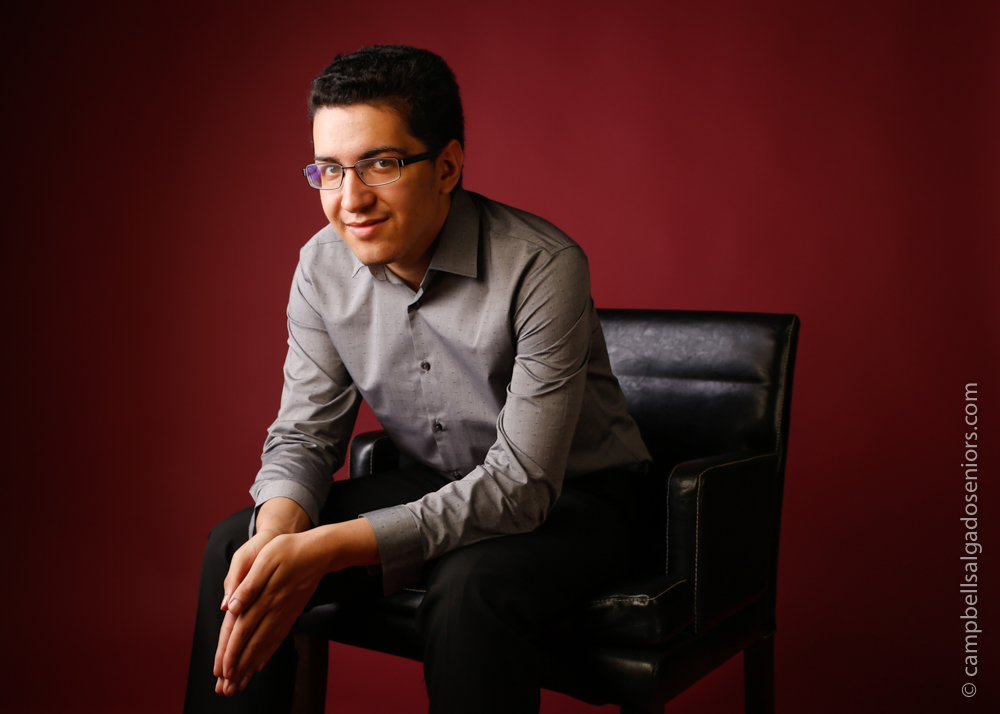 Portrait of young man against a rouge background by Portland photographers - senior pictures at Campbell Salgado Studio in Portland, Oregon.