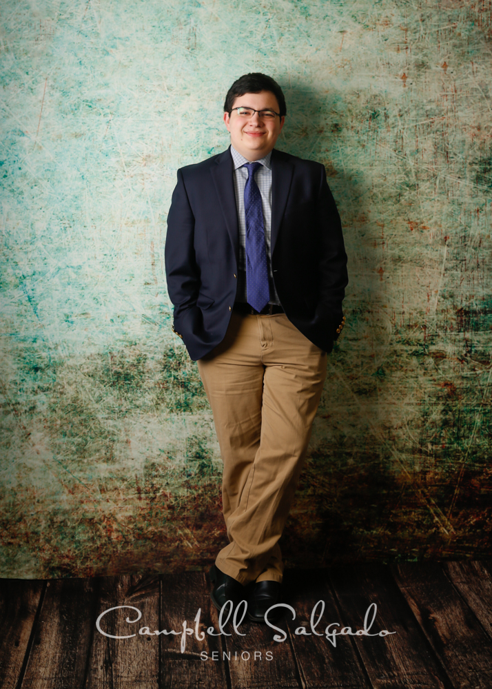 Senior photos, Portland Oregon of young man in front of a weathered green background by photographers at Campbell Salgado Studio.