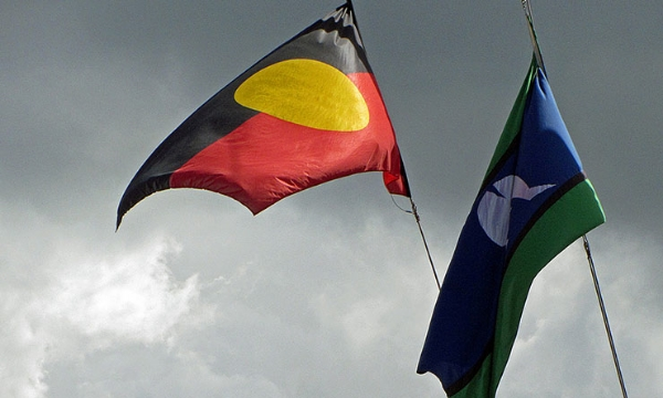 The Aboriginal and Torres Strait Islander flags, pictured outside the National Maritime Museum in Sydney. (Image: Newtown graffiti, Flickr)