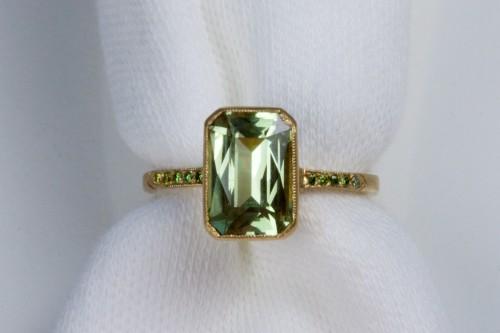 A ring designed by Sonoma California designer,Jennifer Dawes for ANZA Gems with a 3.00 carat Kenyan Kiwi garnet scissor cut center gem and green diamonds in 18k gold.