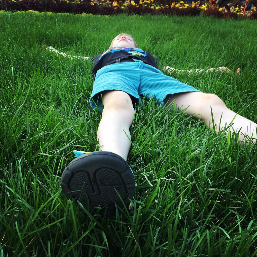 boy-relaxing-grass-savasana.jpg