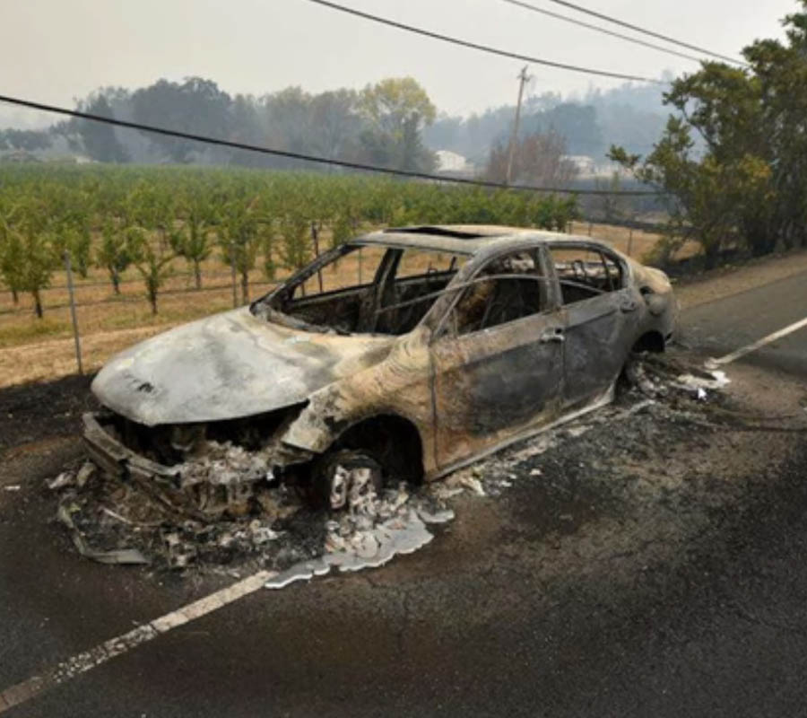 A car in Santa Rosa fairly melted into the pavement, yet is surrounded by asphalt and greenery