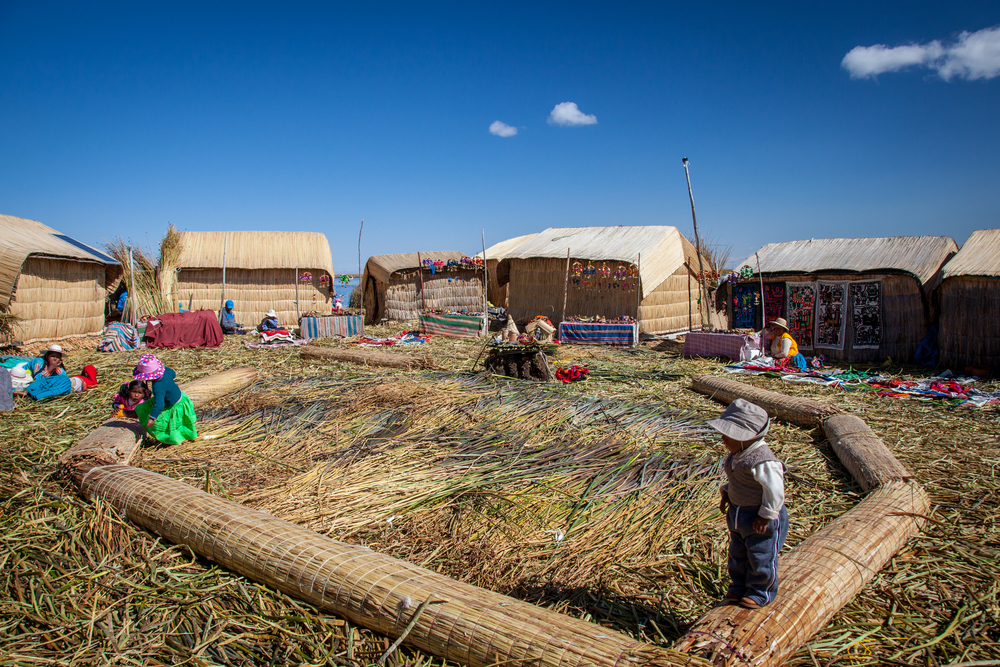 Children playing on rolled up reed mats