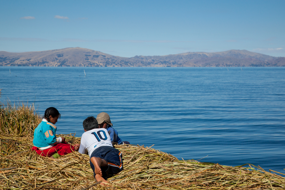 Children playing on the Uros with the Chucuito Peninsula in the background