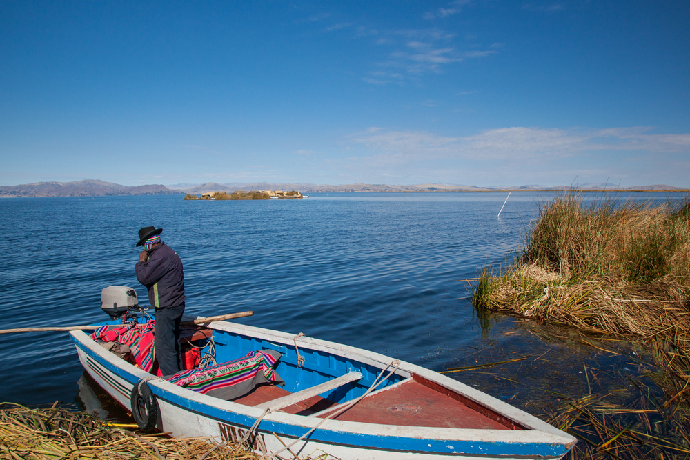 Jose and the boat that brought us to the Uros Islands.  Another floating island can be seen in the distance.