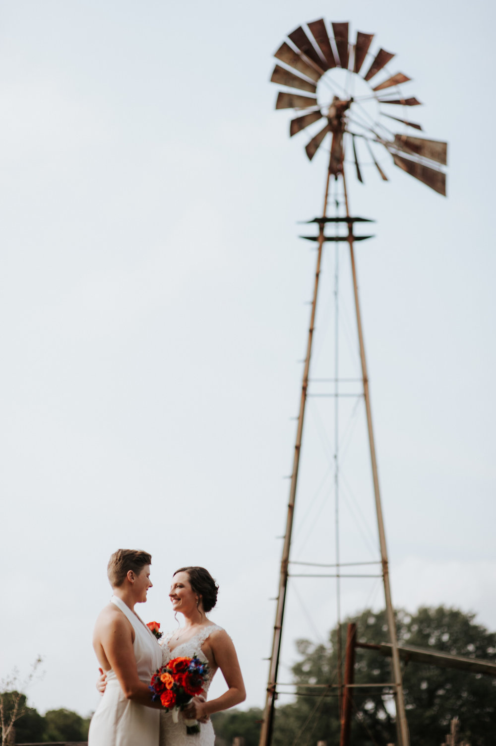 Two brides under windmill at Ranch Austin wedding