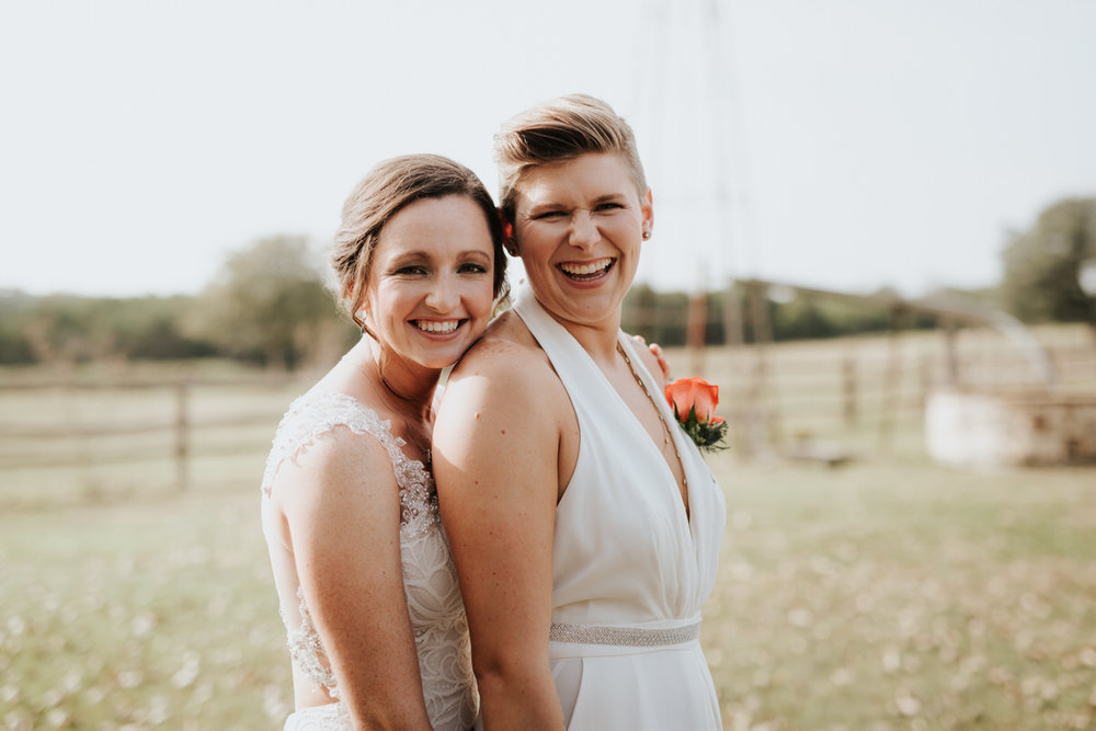 Two brides laughing in field at Ranch Austin wedding