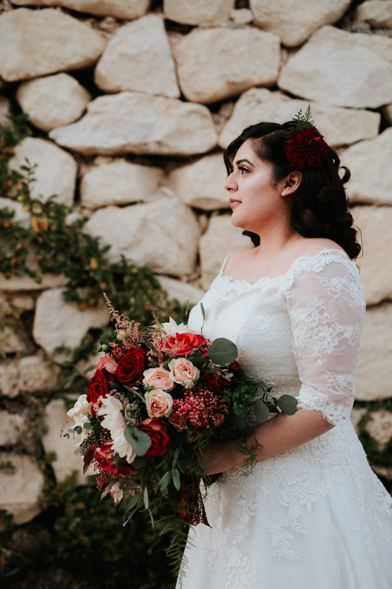 Bride in front of stone house with rose bouquet