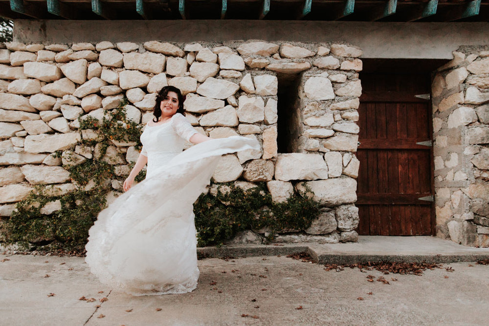 Bride twirling her dress in front of stone house