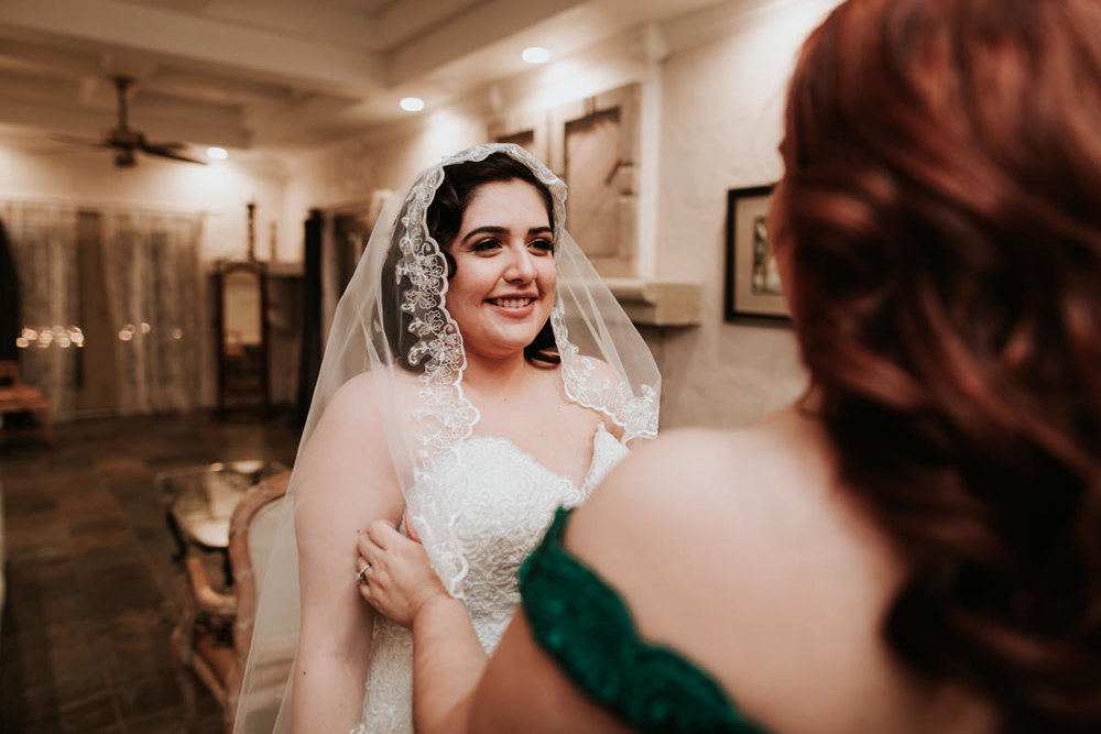 Bride putting veil on